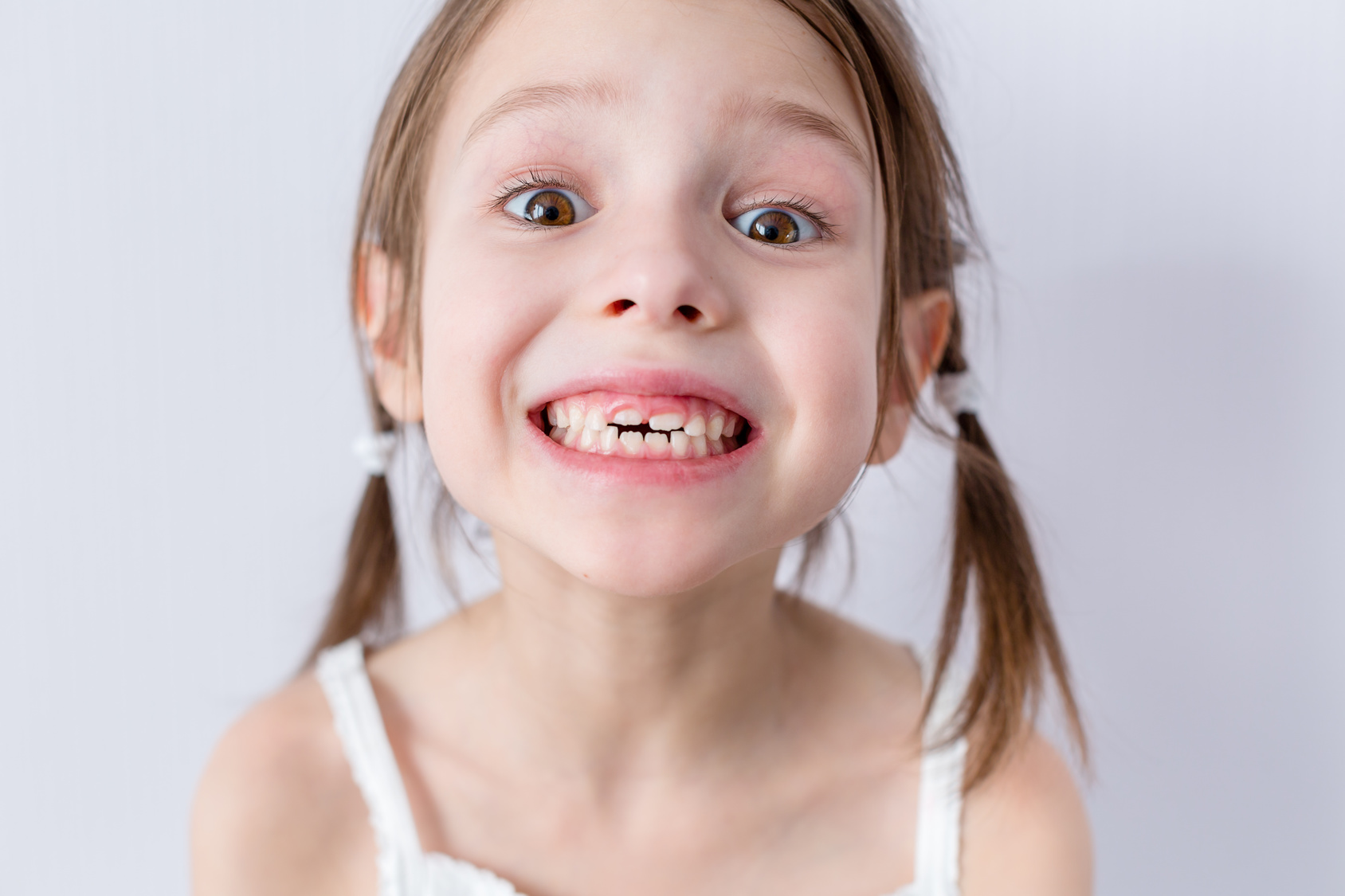Close up portrait of preschooler girl with open mouth without milk tooth
